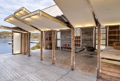 Since this Norwegian boathouse was in a remote location where materials were not easily accessible, the architects focused on using recycled materials. The building is made of wood salvaged from the original 18th-century structure that stood on the site and an old farmhouse nearby. The walls lift upwards (above) to open up the interior to the deck and the river.