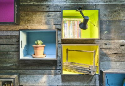 Tyin uses little inexpensive touches to incorporate fun into their found-material designs, such as brightly painted wooden boxes that serve as bookshelves and display niches.