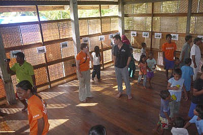 Eco-friendly place: Children exploring the community learning centre building as Hall (centre) chats with a Camp Borneo staff member in Pulau Mantanani.