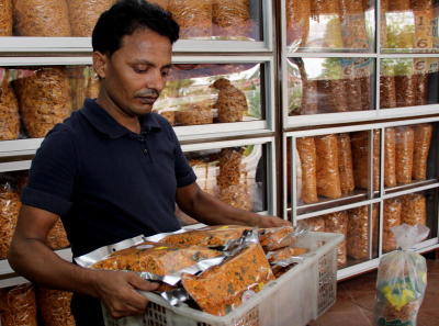 Popular treat: A worker carrying a basket of murukku at Kampung Kacang Putih in Ipoh.