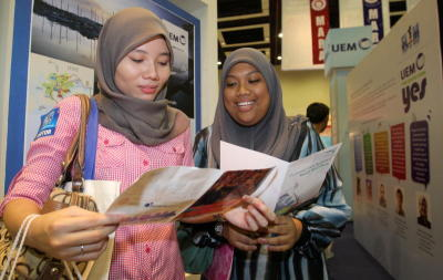 Options abound: Siti (right) and Norhafidah reading brochures at the job fair in
