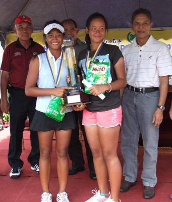 Superb performance: Indonesia's Shevita Aulana (front) and Hanna Levina are all smiles after receving their trophy from Tuanku Syed Badarudin (right) for winning the Under-14 doubles title in the Perlis-milo Junior International tennis tournament in Kangar