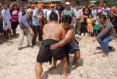 Muscle men: Two men taking part in the Payu competition as Sikie, seen with the crowd at left, gestures excitedly.