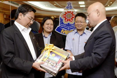 Marking the link: Roslan (left) presenting a set of CD and book on Petaling Jaya to Isao after both mayors inked the sister cities
