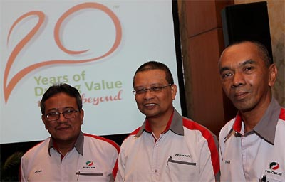 Perodua executive director, Zainal Abidin Ahmad, MD, Datuk Aminar Rashid Salleh and Perodua director, Zahari Husin posing for photographers with their 20-year logo. - THE STAR/SAMUEL PNG