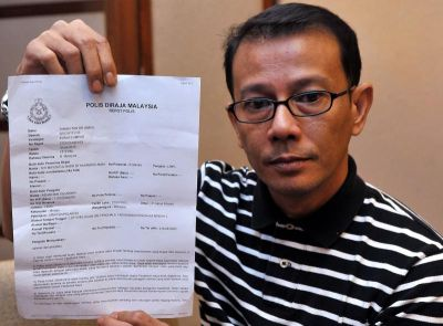 Actor Azhar Sulaiman displaying his police report made over the hacking of his Facebook account