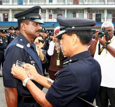 <b>Honoured:</b> Sjn Gunasegran (left) receiving his stripes from SAC Zulkapli.