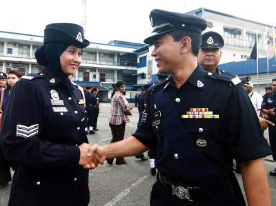 <b>Good job!:</b> Sjn Jamariah (left) being congratulated by a fellow policeman after receiving her promotion stripes.