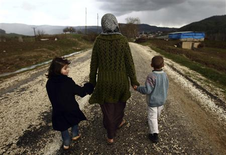 Sawssan Abdelwahab, who fled Idlib in Syria, walks with her children outside the refugees camp near the Turkish-Syrian border in the southeastern city of Yayladagi in this February 16, 2012 file picture. REUTERS/Zohra Bensemra/Files