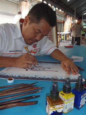 Beauty of calligraphy: Zuhudi writing with a sharpened resam twig at the Malay Heritage Showcase of George Town Festival 2013.